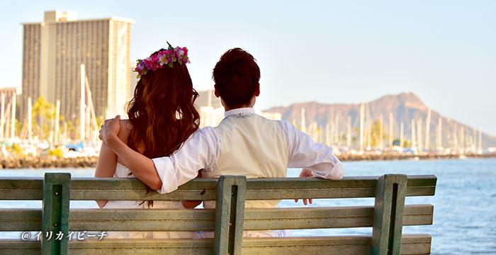 ビーチのベンチで肩を寄せ合うカップル